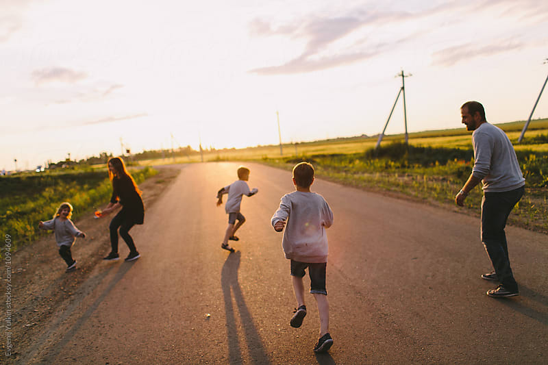 Family with three boys playing on the road  by Evgenij Yulkin for Stocksy United