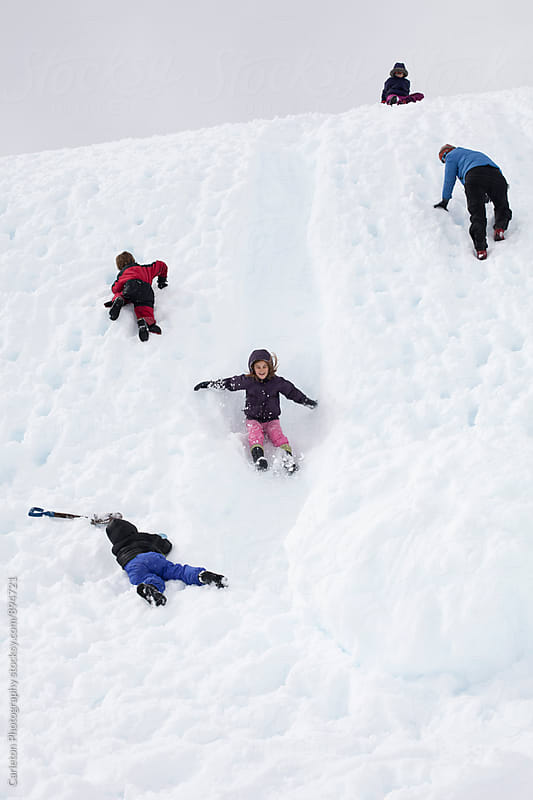 Mom and four kids enjoying a snow slide by Carleton Photography for Stocksy United