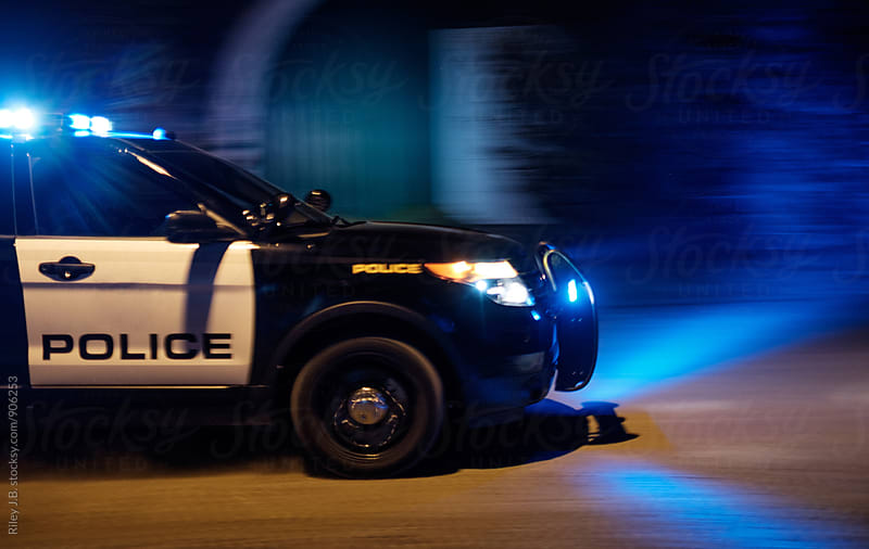 A police vehicle driving fast with red & blue lights flashing. by Riley J.B. for Stocksy United