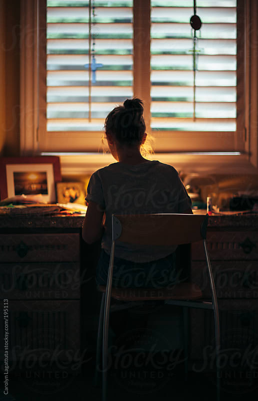 Young teen sitting at the desk doing homework in the evening by Carolyn Lagattuta for Stocksy United