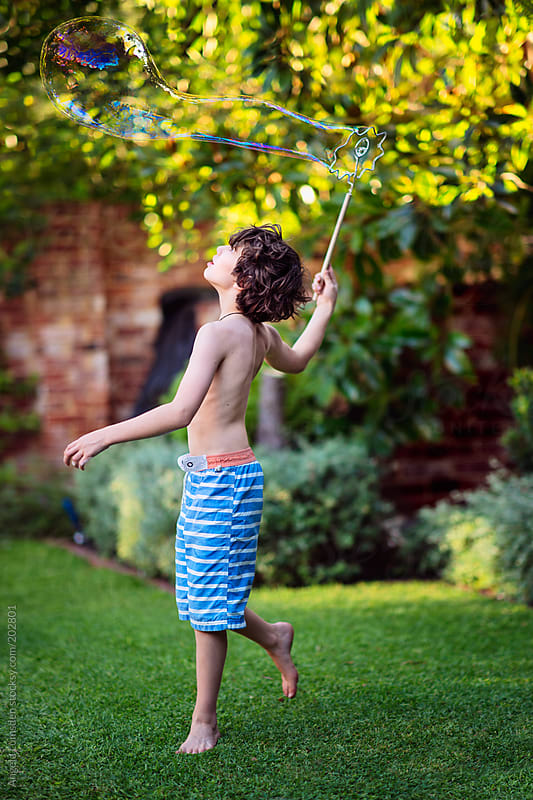 Boy playing with bubbles in a garden in summer by Angela Lumsden for Stocksy United