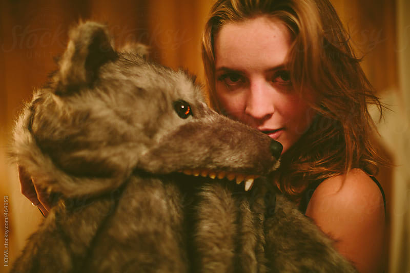 Young blonde woman poses next to wolf costume  by HOWL for Stocksy United
