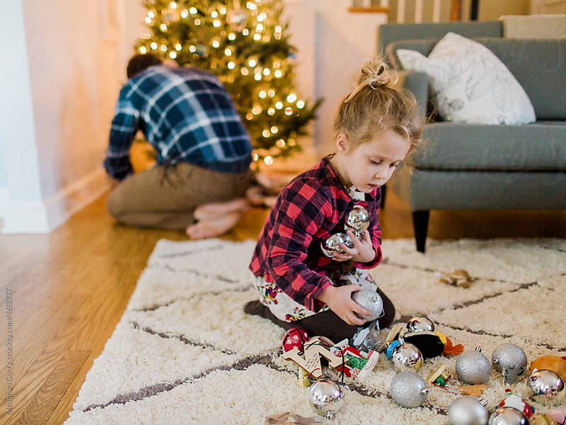 Father and daughter decorate a Christmas tree by Meaghan Curry for Stocksy United