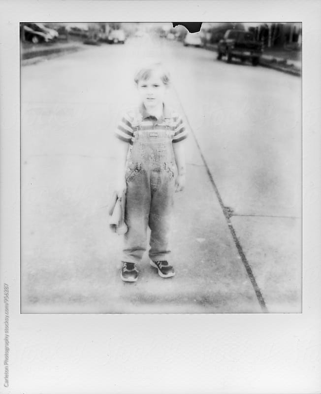 Old timey portrait of boy in overalls standing in the street by Carleton Photography for Stocksy United