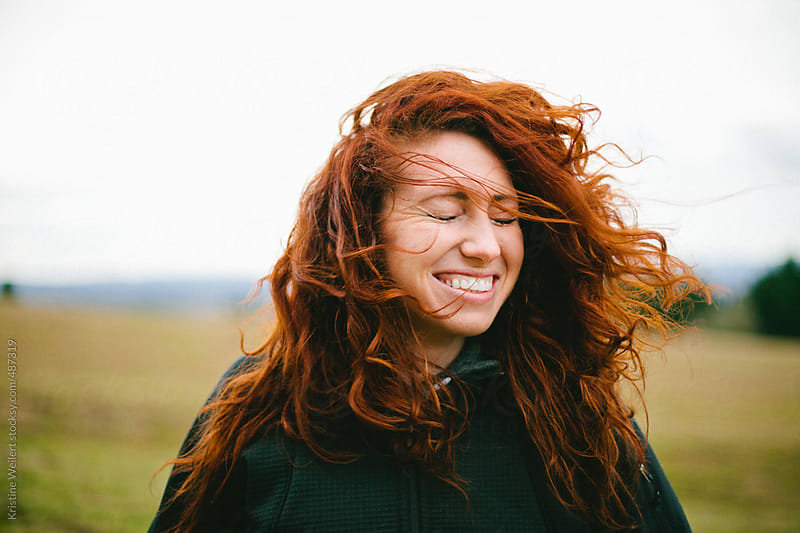 Woman's Red Curly Hair Being Blown in the Wind by Kristine Weilert for Stocksy United