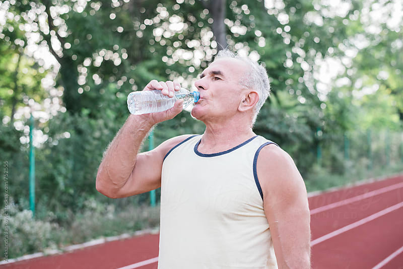 Middle-aged Man Drinking Water After Jogging by Aleksandra Jankovic for Stocksy United
