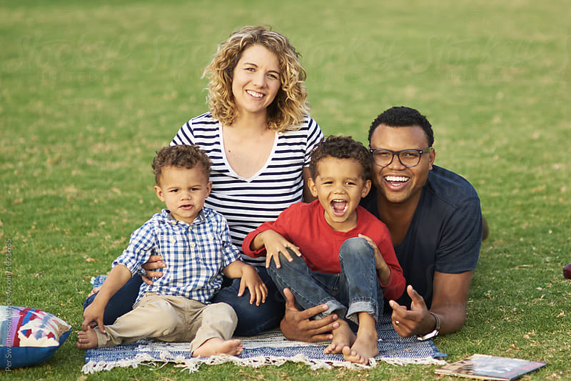 Happy mixed family having fun in the park with their sons by Per Swantesson for Stocksy United
