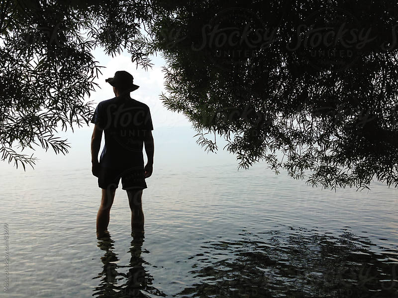 Silhouette of a Man Standing in a Shallow Water by Mosuno for Stocksy United