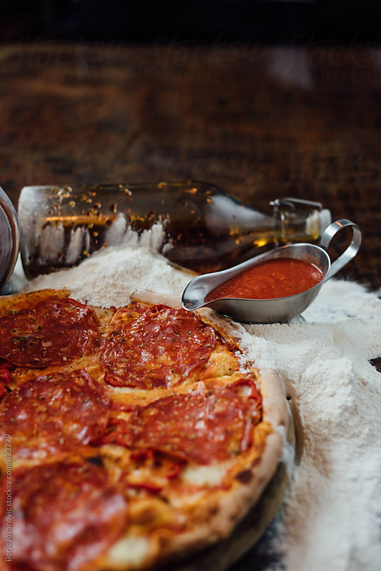 Sausage pizza arranged with olive bottle and tomato sauce by Boris Jovanovic for Stocksy United