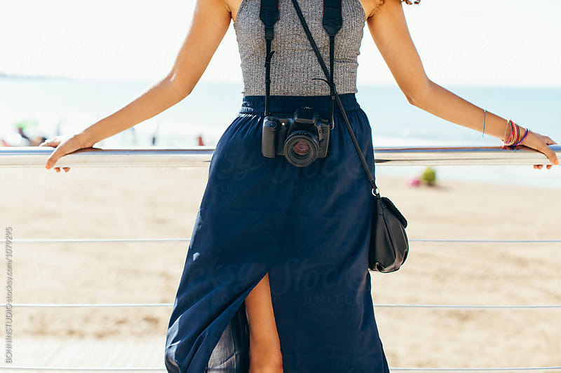 Closeup of a female tourist with her camera in front of the beach.  by BONNINSTUDIO for Stocksy United