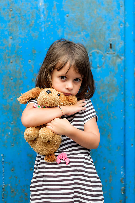 Girl holding her toy with a suspicious attitude by German Parga for Stocksy United