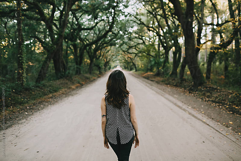 Girl looking down the tree lined road from behind by Sara K Byrne Photography for Stocksy United