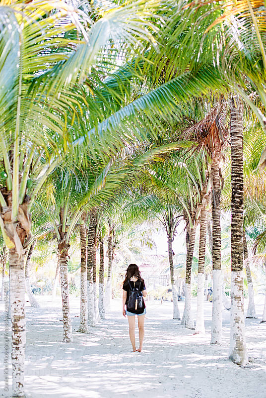 Woman walking in between palm trees by Daniel Kim Photography for Stocksy United