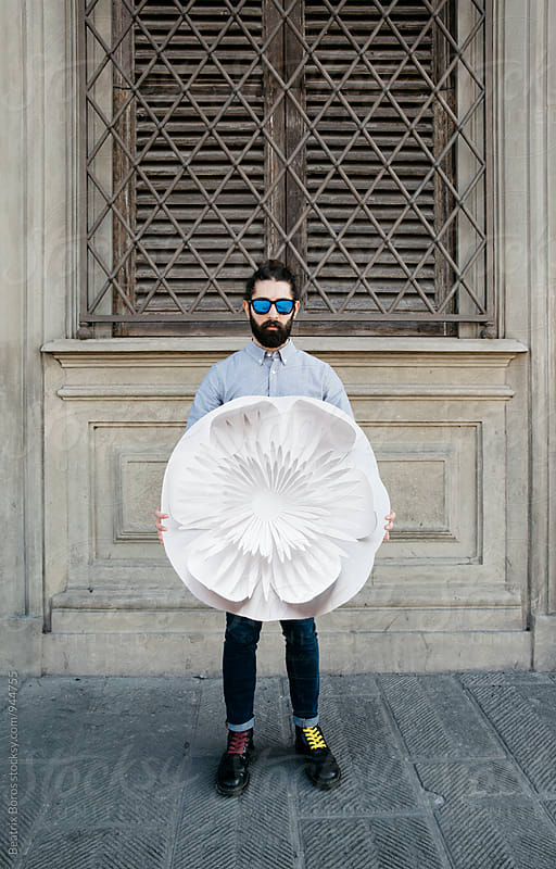 Bearded man holding a big paper flower  by Beatrix Boros for Stocksy United