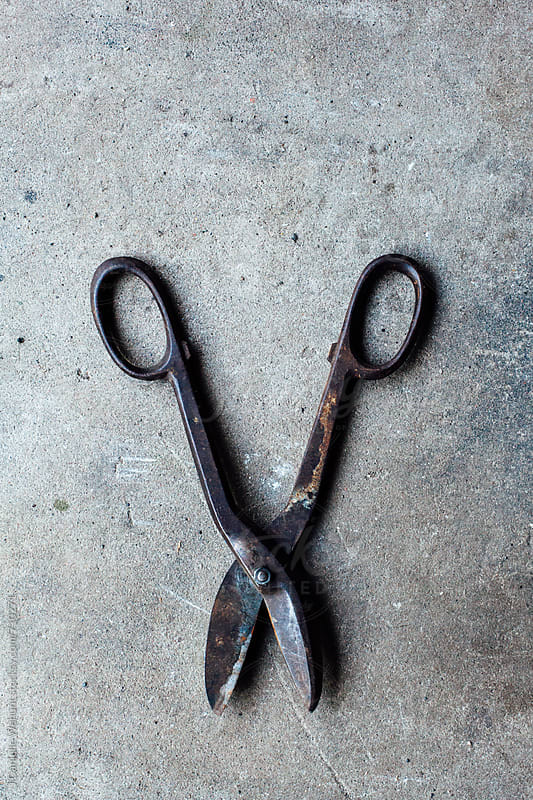 Tin nippers or wire cutters laying on concrete. by J Danielle Wehunt for Stocksy United