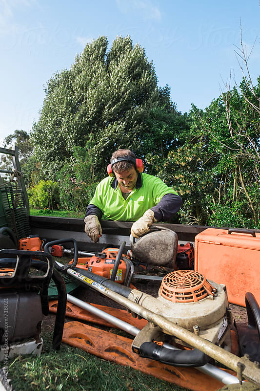 Man refueling chainsaw by Rowena Naylor for Stocksy United