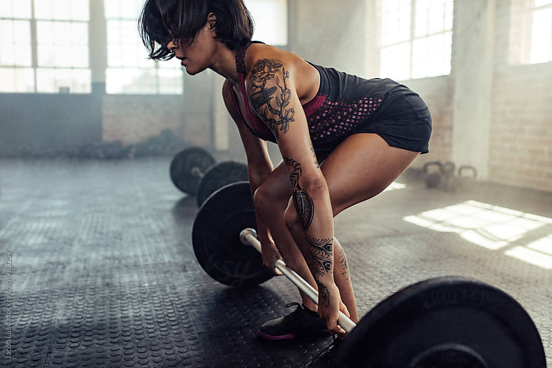 Tattooed woman working out with barbell at gym by Jacob Lund for Stocksy United