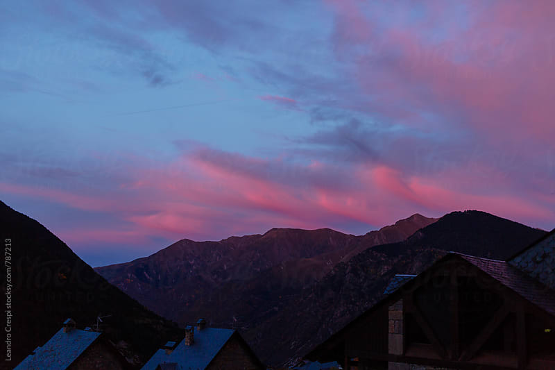 Beautiful pink clouds behind a mountain range by Leandro Crespi for Stocksy United