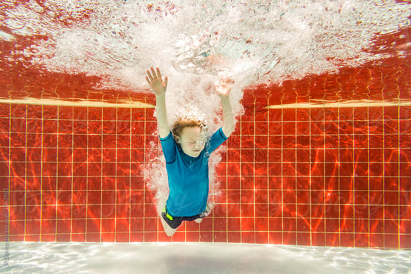 Underwater Boy Jumping Into Sunny All Inclusive Luxury Resort Pool on Caribbean Vacation by JP Danko for Stocksy United