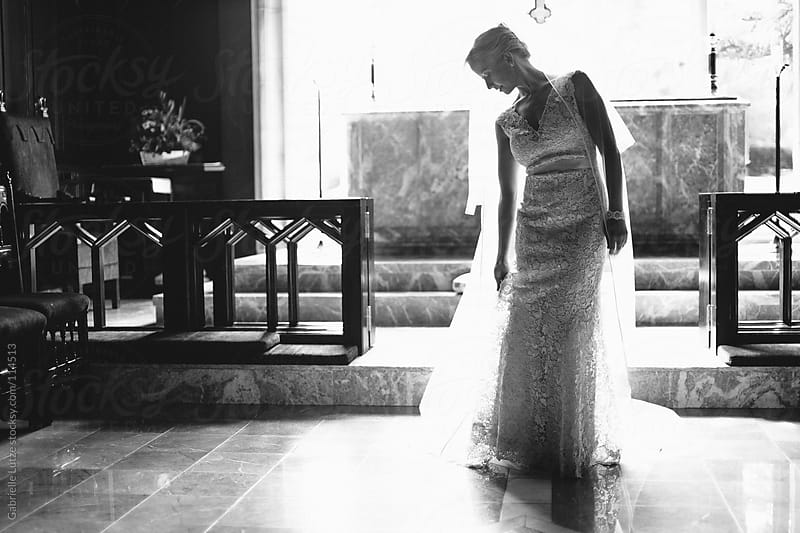 Bride on Alter in Black and White by Gabrielle Lutze for Stocksy United