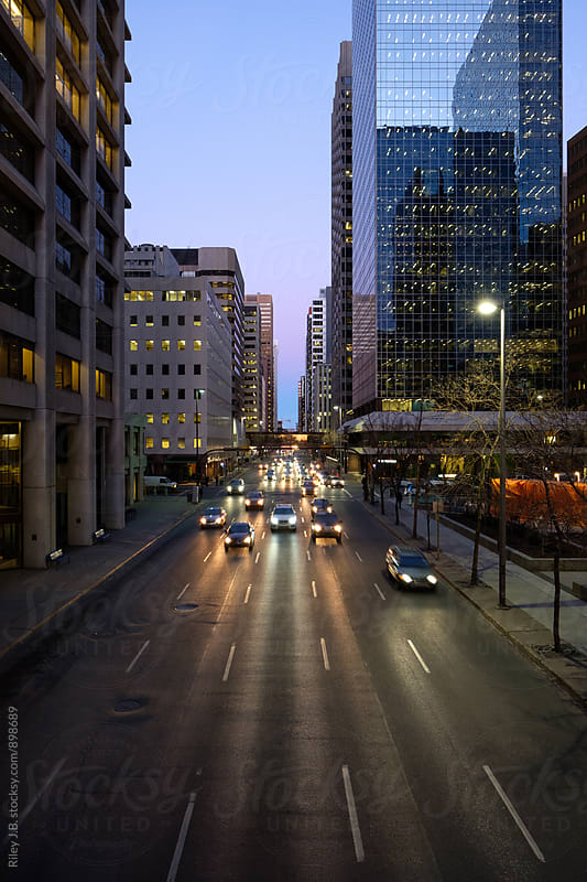 A busy downtown street with vehicles approaching at dawn by Riley Joseph for Stocksy United