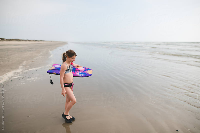 Young girl about to boogie board by Courtney Rust for Stocksy United