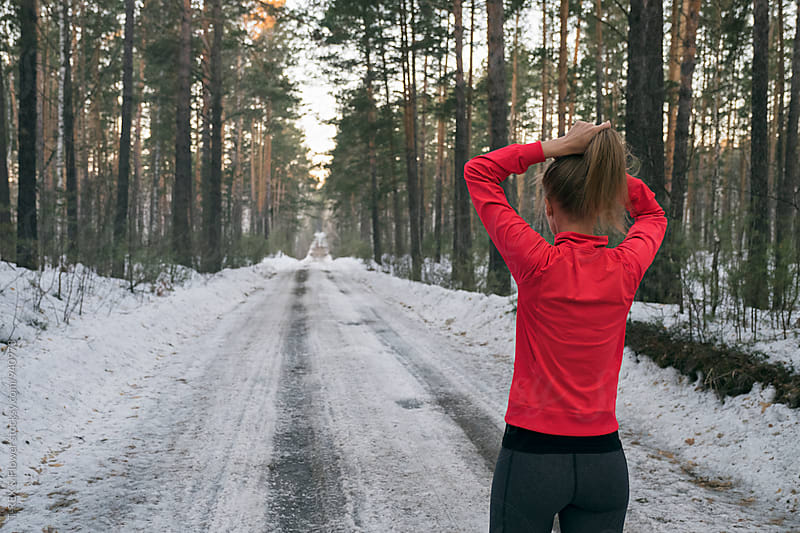 Back view of female athlete on snowy road by T-REX & Flower for Stocksy United