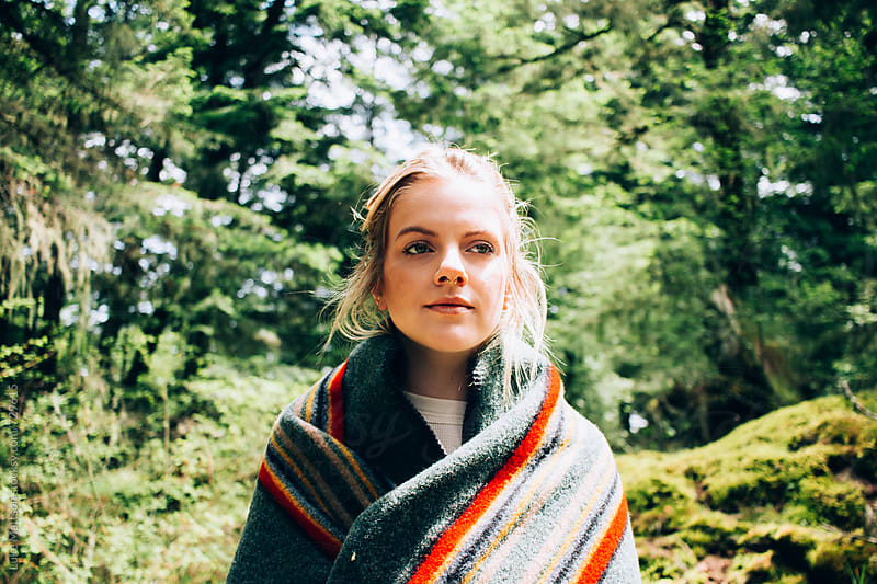 Young Blonde Woman Wrapped In Wool Blanket Standing In Mossy Wooded Area by Luke Mattson for Stocksy United