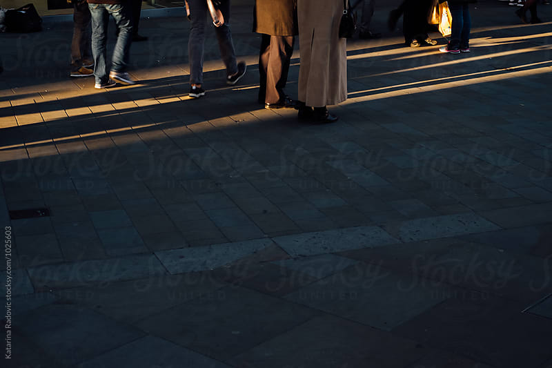 Unrecognizable People Walking Down the Street at Sunset by Katarina Radovic for Stocksy United