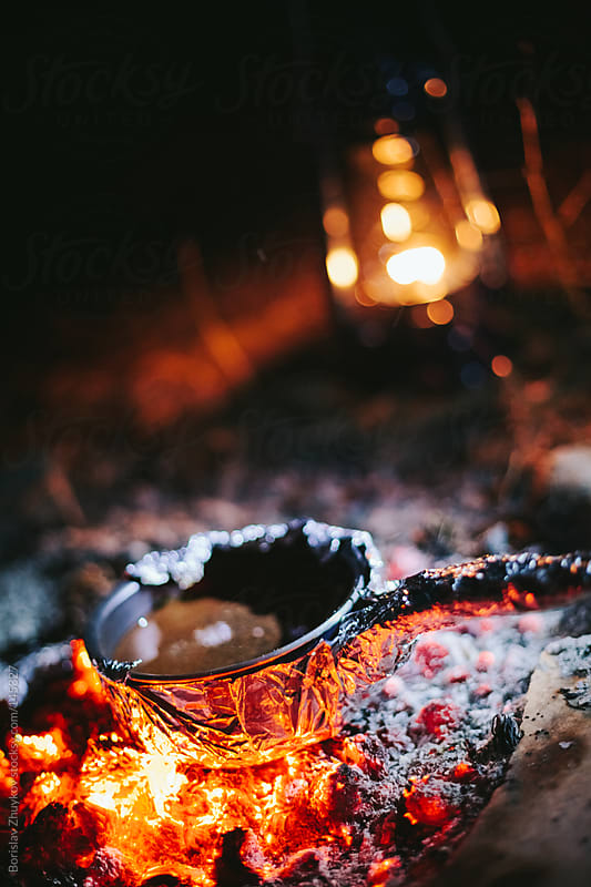 Camp fire and small pot with coffee  by Borislav Zhuykov for Stocksy United