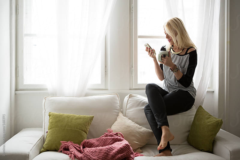 Woman Using Her Mobile Phone at Home by Lumina for Stocksy United