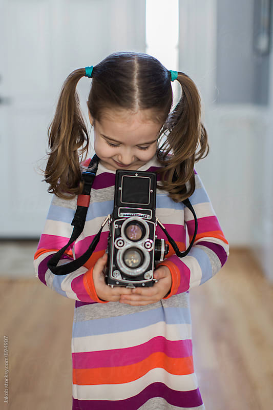 Cute young girl with pigtails using a vintage camera by Jakob for Stocksy United