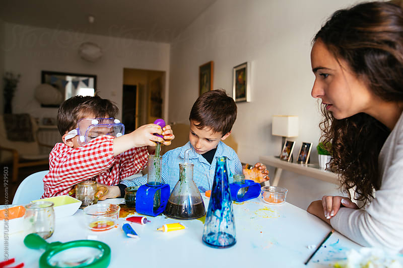 Mother and sons making experiments with liquids at home. by BONNINSTUDIO for Stocksy United