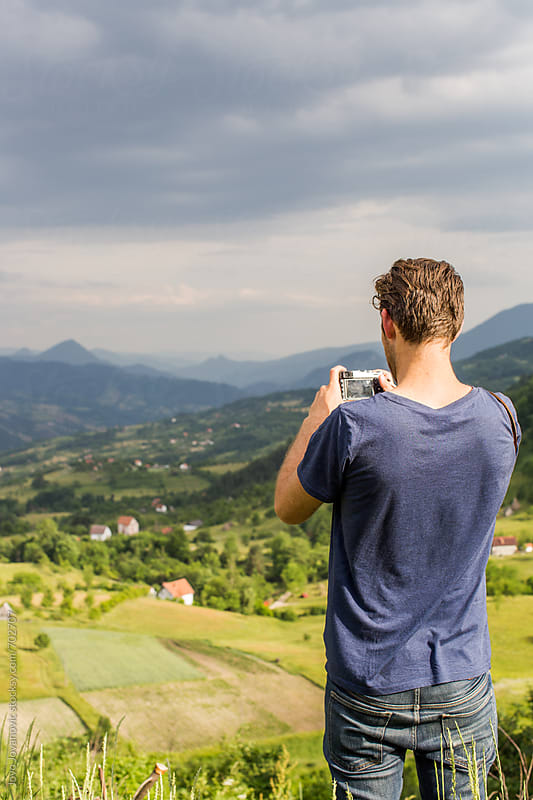 Man taking a photo of beautiful Bosnian mountains in background by Jovo Jovanovic for Stocksy United