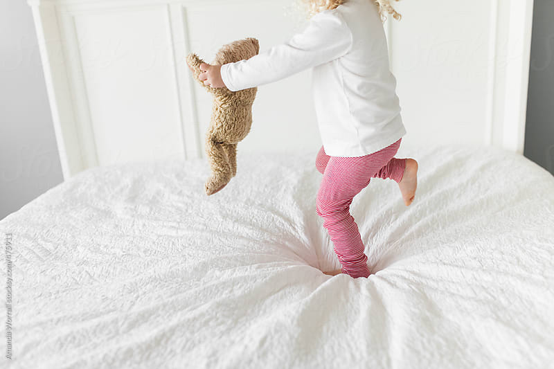 Young girl wearing red and white striped pajamas playing with teddy bear by Amanda Worrall for Stocksy United