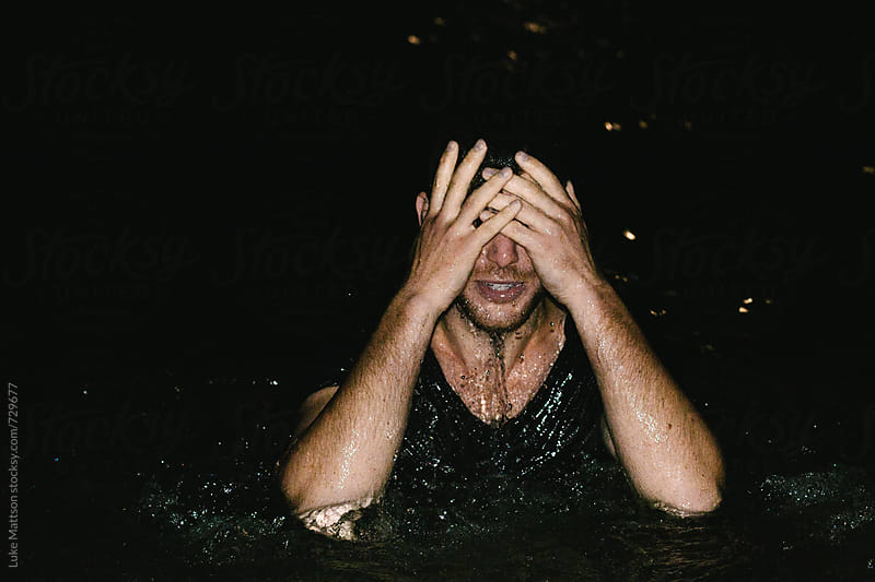 Man Standing In Chest Deep Water Holding Hands Over Face  by Luke Mattson for Stocksy United