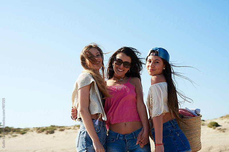 Three girlfriends on beach by Guille Faingold for Stocksy United
