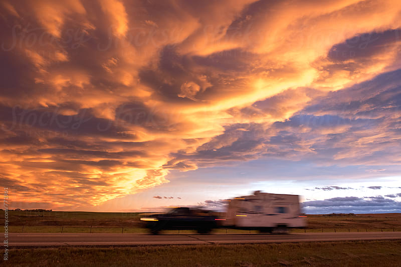 A truck towing a camper drives by with an impressive sunset by Riley J.B. for Stocksy United