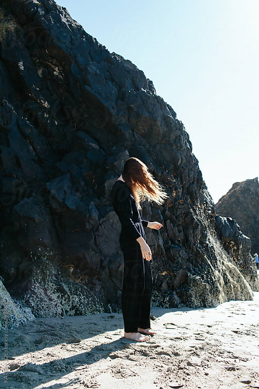 Girl standing on a beach by a huge rock with wind in her hair by KATIE + JOE for Stocksy United