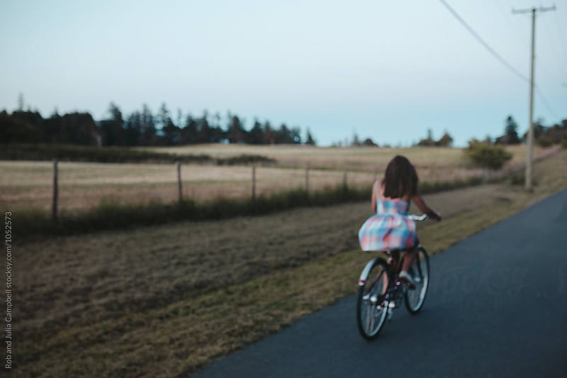 Young happy caucasian girl riding cruiser bike on country road by Rob and Julia Campbell for Stocksy United