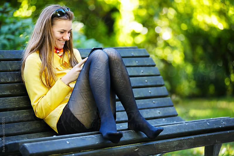 Young woman using smart phone outdoors by Ilya for Stocksy United