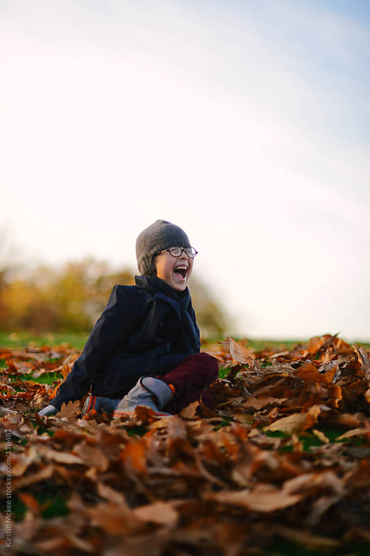 Boy grinning while sitting on a pile of leaves by Kirstin Mckee for Stocksy United