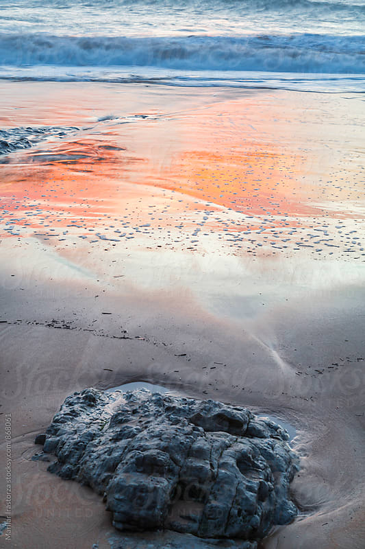Colors of sunset reflected in the wet sand of a beach by Marilar Irastorza for Stocksy United