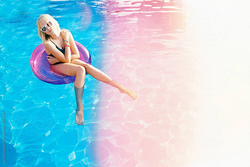 bonde girl with short hair in pink floatie with blue pool and pink light leak on film by wendy laurel for Stocksy United