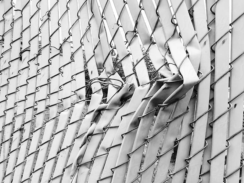 Detail of broken chain-link fence by Paul Edmondson for Stocksy United