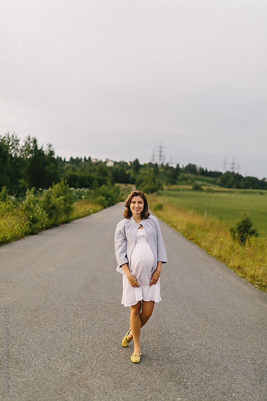 Pregnant female standing on the  road by Evgenij Yulkin for Stocksy United