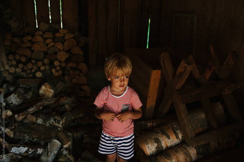 Blonde boy stands in a wood shed. by Julia Forsman for Stocksy United