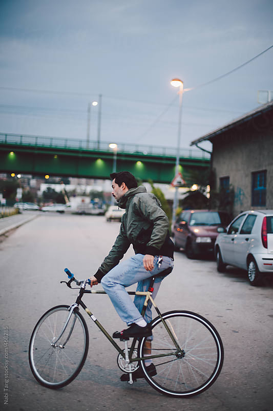Young man riding a bicycle on quiet street in the evening by Nabi Tang for Stocksy United