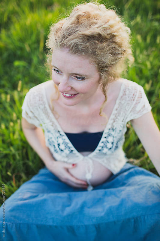 Smiling pregnant woman sitting on a grass by michela ravasio for Stocksy United