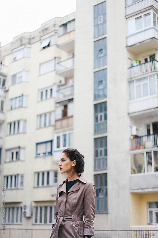 Beautiful brunette standing in front of a building  by Marija Kovac for Stocksy United